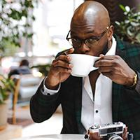 Man sits at a table sipping coffee